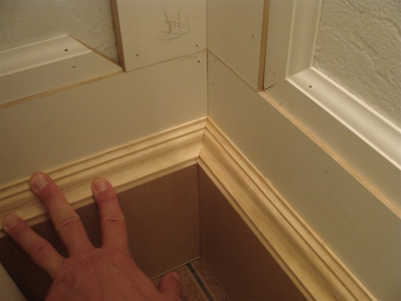 half bathroom renovation installing the baseboard cap molding the